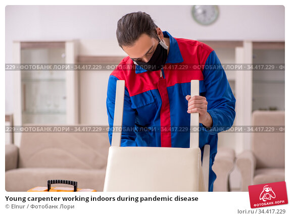 Young carpenter working indoors during pandemic disease. Стоковое фото, фотограф Elnur / Фотобанк Лори