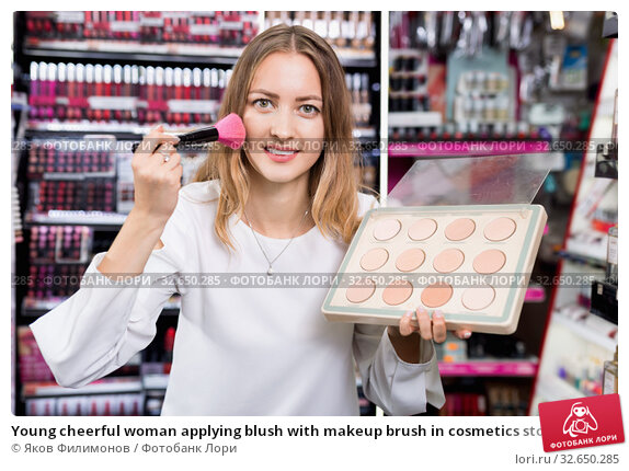 Купить «Young cheerful woman applying blush with makeup brush in cosmetics store», фото № 32650285, снято 19 октября 2019 г. (c) Яков Филимонов / Фотобанк Лори
