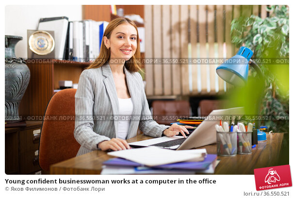 Young confident businesswoman works at a computer in the office. Стоковое фото, фотограф Яков Филимонов / Фотобанк Лори