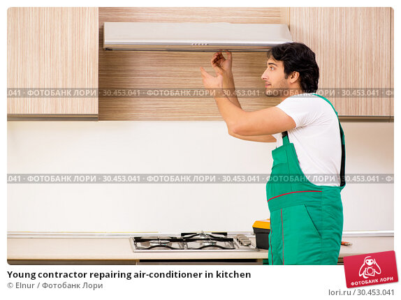 Young contractor repairing air-conditioner in kitchen. Стоковое фото, фотограф Elnur / Фотобанк Лори