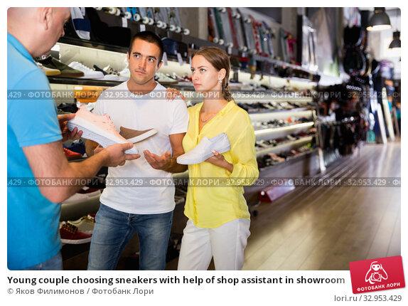 Young couple choosing sneakers with help of shop assistant in showroom. Стоковое фото, фотограф Яков Филимонов / Фотобанк Лори