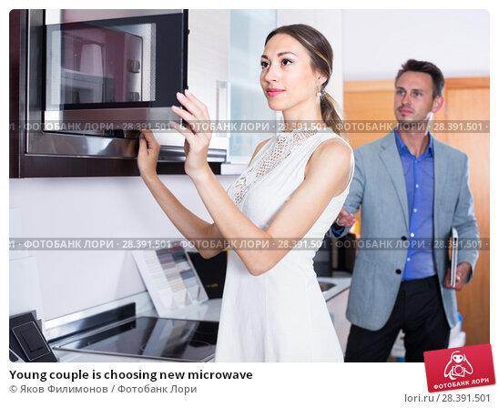 Купить «Young couple is choosing new microwave», фото № 28391501, снято 15 июня 2017 г. (c) Яков Филимонов / Фотобанк Лори