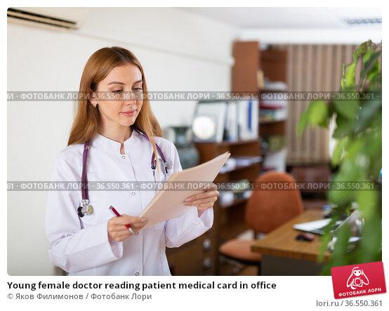 Young female doctor reading patient medical card in office. Стоковое фото, фотограф Яков Филимонов / Фотобанк Лори