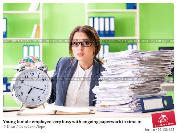 Купить «Young female employee very busy with ongoing paperwork in time m», фото № 29138625, снято 8 июня 2018 г. (c) Elnur / Фотобанк Лори