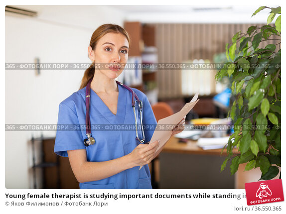 Young female therapist is studying important documents while standing in the office. Стоковое фото, фотограф Яков Филимонов / Фотобанк Лори