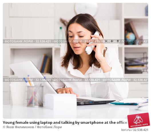 Купить «Young female using laptop and talking by smartphone at the office», фото № 32538421, снято 1 мая 2018 г. (c) Яков Филимонов / Фотобанк Лори