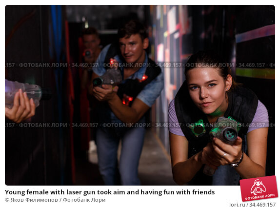 Young female with laser gun took aim and having fun with friends. Стоковое фото, фотограф Яков Филимонов / Фотобанк Лори