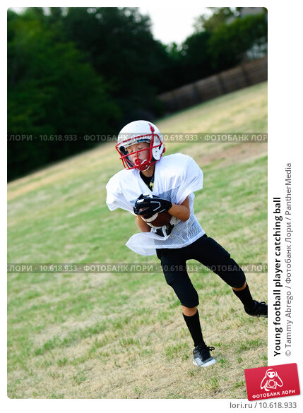 Young football player catching ball. Стоковое фото, фотограф Tammy Abrego / PantherMedia / Фотобанк Лори