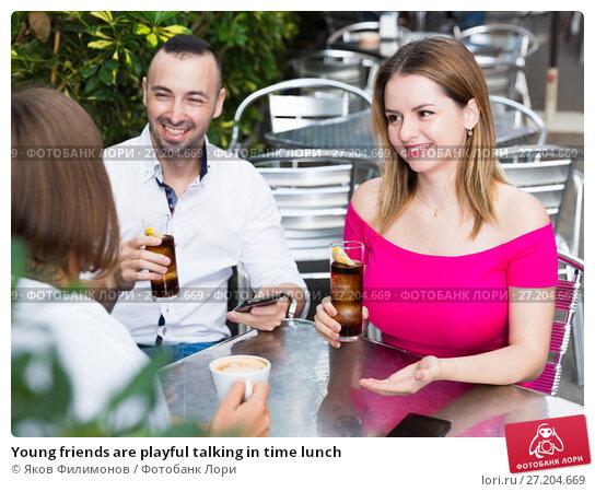 Купить «Young friends are playful talking in time lunch», фото № 27204669, снято 18 октября 2017 г. (c) Яков Филимонов / Фотобанк Лори