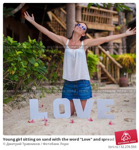 """Купить «Young girl sitting on sand with the word """"Love"""" and spread her arms», фото № 32276593, снято 10 мая 2013 г. (c) Дмитрий Травников / Фотобанк Лори"""