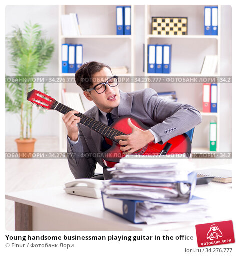 Young handsome businessman playing guitar in the office. Стоковое фото, фотограф Elnur / Фотобанк Лори