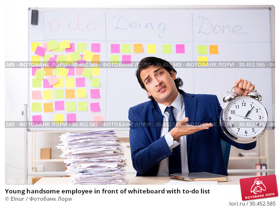 Young handsome employee in front of whiteboard with to-do list. Стоковое фото, фотограф Elnur / Фотобанк Лори