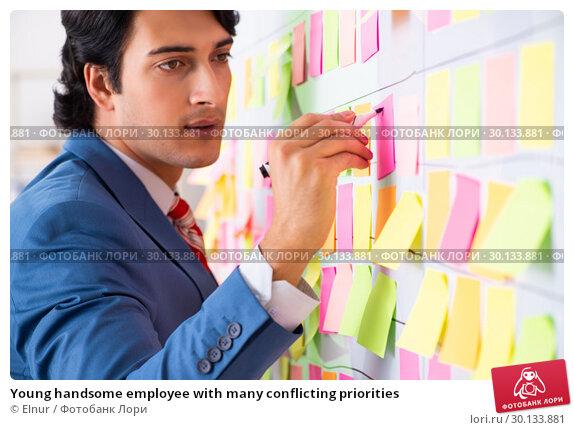 Купить «Young handsome employee with many conflicting priorities», фото № 30133881, снято 16 октября 2018 г. (c) Elnur / Фотобанк Лори