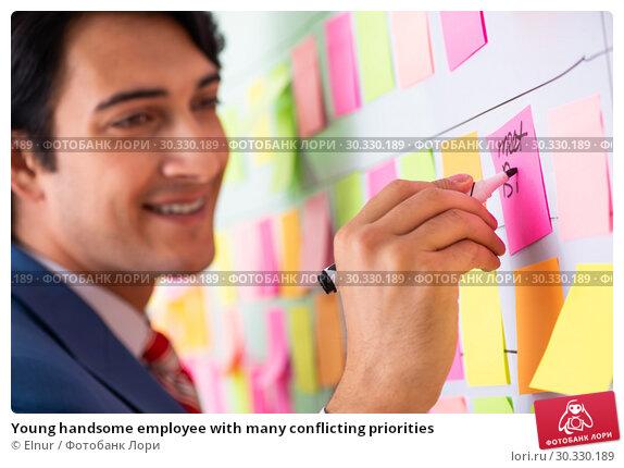 Купить «Young handsome employee with many conflicting priorities», фото № 30330189, снято 16 октября 2018 г. (c) Elnur / Фотобанк Лори