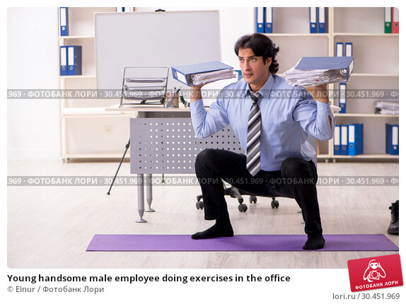 Young handsome male employee doing exercises in the office. Стоковое фото, фотограф Elnur / Фотобанк Лори