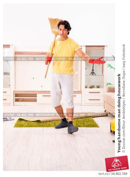 Young handsome man doing housework. Стоковое фото, фотограф Zoonar.com/Elnur Amikishiyev / easy Fotostock / Фотобанк Лори