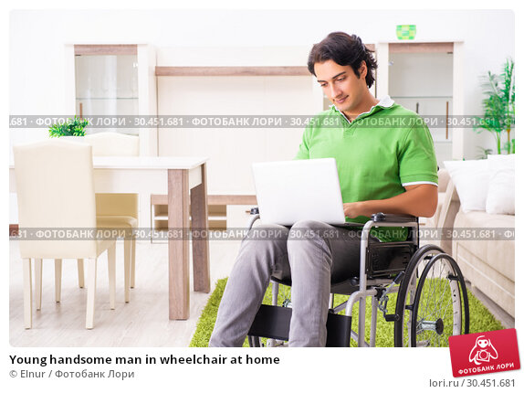 Young handsome man in wheelchair at home. Стоковое фото, фотограф Elnur / Фотобанк Лори