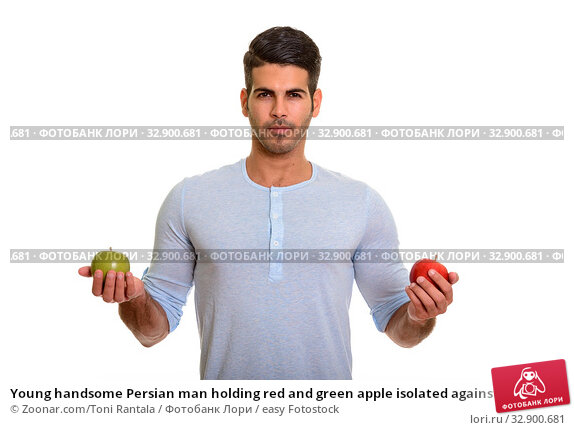 Young handsome Persian man holding red and green apple isolated against white background. Стоковое фото, фотограф Zoonar.com/Toni Rantala / easy Fotostock / Фотобанк Лори