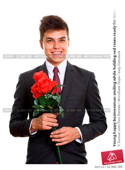 Young happy businessman smiling while holding red roses ready for Valentine's day. Стоковое фото, фотограф Zoonar.com/Toni Rantala / easy Fotostock / Фотобанк Лори