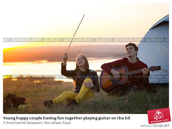 Купить «Young happy couple having fun together playing guitar on the hil», фото № 28420457, снято 14 мая 2018 г. (c) Константин Шишкин / Фотобанк Лори