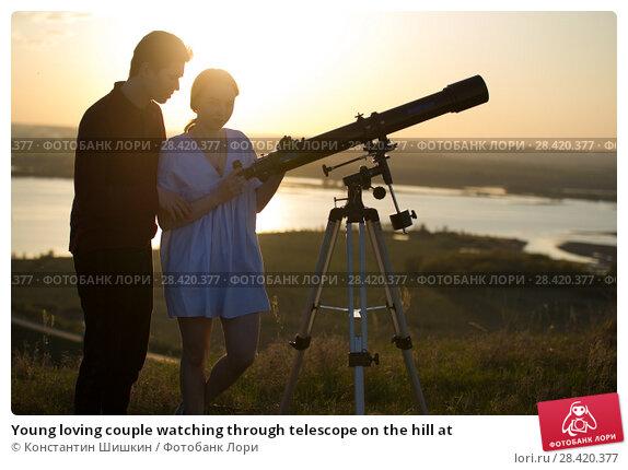 Купить «Young loving couple watching through telescope on the hill at», фото № 28420377, снято 14 мая 2018 г. (c) Константин Шишкин / Фотобанк Лори