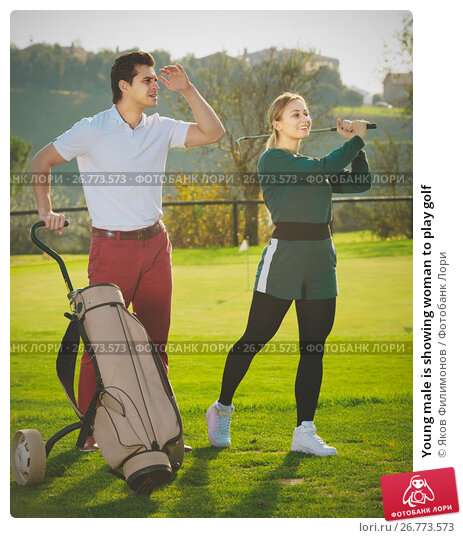 Young male is showing woman to play golf, фото № 26773573, снято 23 сентября 2017 г. (c) Яков Филимонов / Фотобанк Лори