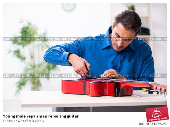 Young male repairman repairing guitar. Стоковое фото, фотограф Elnur / Фотобанк Лори