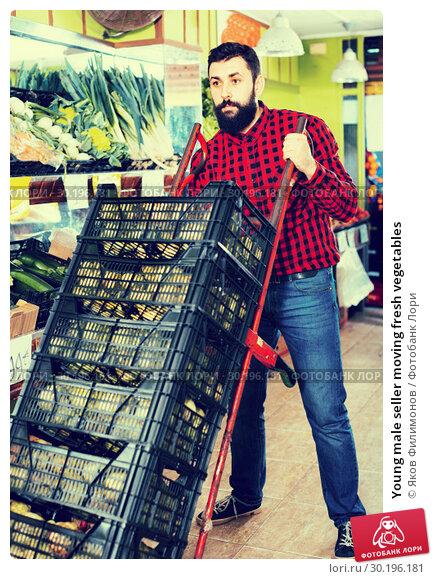 Купить «Young male seller moving fresh vegetables», фото № 30196181, снято 15 ноября 2016 г. (c) Яков Филимонов / Фотобанк Лори