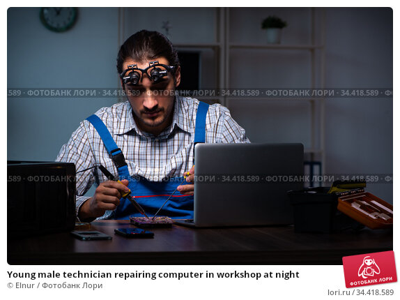 Young male technician repairing computer in workshop at night. Стоковое фото, фотограф Elnur / Фотобанк Лори
