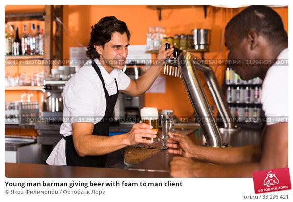 Купить «Young man barman giving beer with foam to man client», фото № 33296421, снято 28 августа 2019 г. (c) Яков Филимонов / Фотобанк Лори