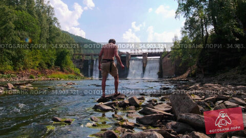 Young man on vacation - watching the waterfalls in the forest. Стоковое видео, видеограф Константин Шишкин / Фотобанк Лори