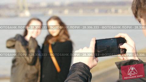 Купить «Young man shoots smiling girlfriends on the waterfront in sunny day», видеоролик № 28306333, снято 21 апреля 2018 г. (c) Константин Шишкин / Фотобанк Лори