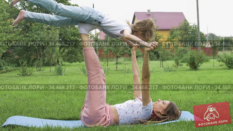 Young mother with dreadlocks and little daughter are doing yoga exercises on grass in the park at the day time. Concept of friendly family and of summer vacation. Стоковое видео, видеограф Ольга Балынская / Фотобанк Лори