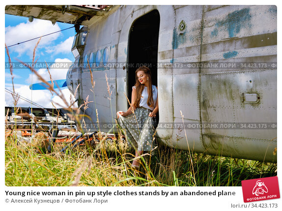 Young nice woman in pin up style clothes stands by an abandoned plane. Стоковое фото, фотограф Алексей Кузнецов / Фотобанк Лори