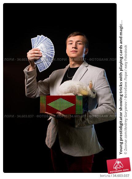 Young prestidigitator showing tricks with playing cards and magic... Стоковое фото, фотограф Zoonar.com/Andrey Guryanov / easy Fotostock / Фотобанк Лори
