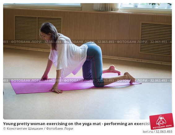 Young pretty woman exercising on the yoga mat - performing an exercising for the loin and spine - bending her loin down. Стоковое фото, фотограф Константин Шишкин / Фотобанк Лори
