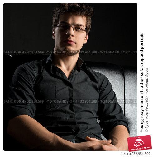 Young sexy man on leather sofa cropped portrait. Стоковое фото, фотограф Гурьянов Андрей / Фотобанк Лори
