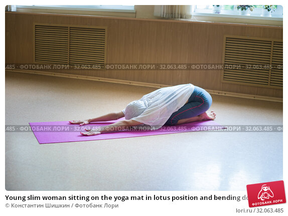 Young slim woman sitting on the yoga mat in lotus position and bending down to the floor - leaning her hands forward - stretching. Стоковое фото, фотограф Константин Шишкин / Фотобанк Лори