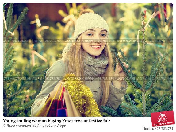 Купить «Young smiling woman buying Xmas tree at festive fair», фото № 26783781, снято 27 мая 2018 г. (c) Яков Филимонов / Фотобанк Лори