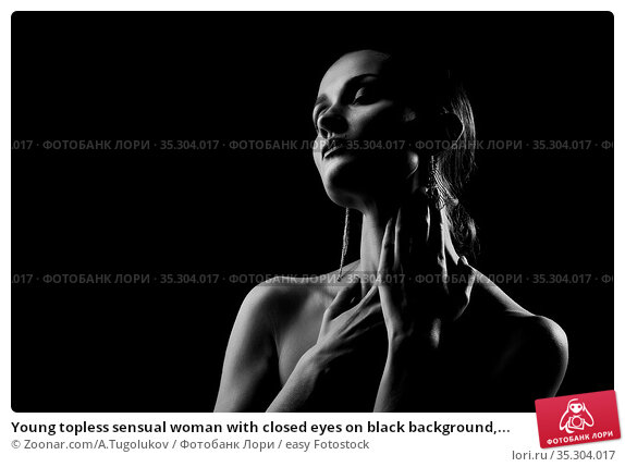 Young topless sensual woman with closed eyes on black background,... Стоковое фото, фотограф Zoonar.com/A.Tugolukov / easy Fotostock / Фотобанк Лори