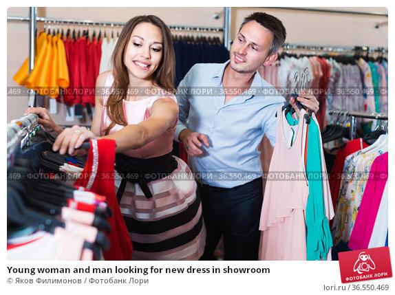 Young woman and man looking for new dress in showroom. Стоковое фото, фотограф Яков Филимонов / Фотобанк Лори