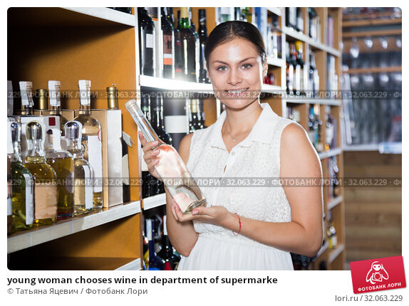 young woman chooses wine in department of supermarke. Стоковое фото, фотограф Татьяна Яцевич / Фотобанк Лори