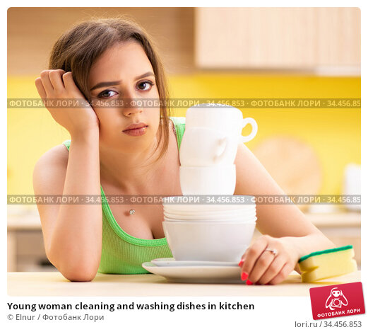 Young woman cleaning and washing dishes in kitchen. Стоковое фото, фотограф Elnur / Фотобанк Лори