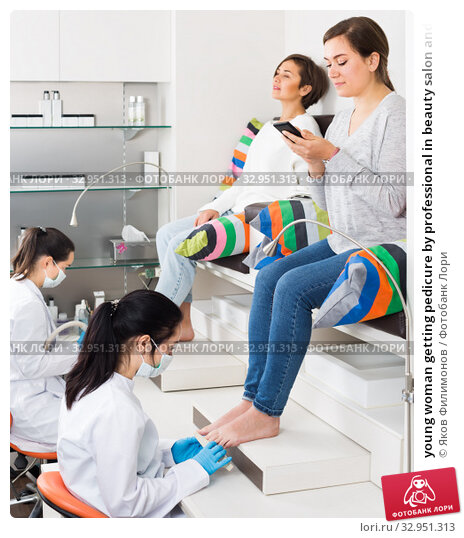 young woman getting pedicure by professional in beauty salon and using phone. Стоковое фото, фотограф Яков Филимонов / Фотобанк Лори