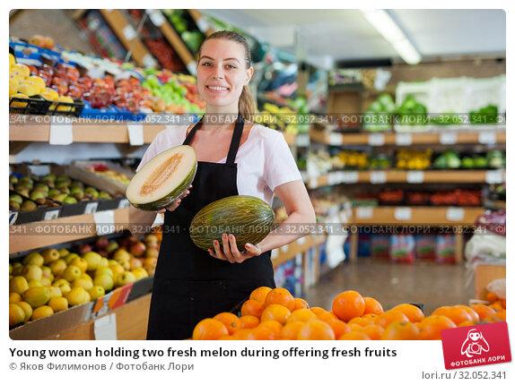 Young woman holding two fresh melon during offering fresh fruits. Стоковое фото, фотограф Яков Филимонов / Фотобанк Лори