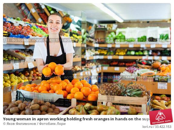 Купить «Young woman in apron working holding fresh oranges in hands on the supermarket», фото № 33422153, снято 27 апреля 2019 г. (c) Яков Филимонов / Фотобанк Лори