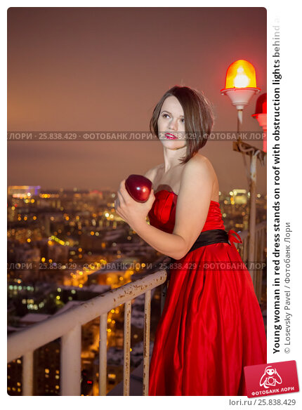 Купить «Young woman in red dress stands on roof with obstruction lights behind and holds red apple», фото № 25838429, снято 13 февраля 2015 г. (c) Losevsky Pavel / Фотобанк Лори