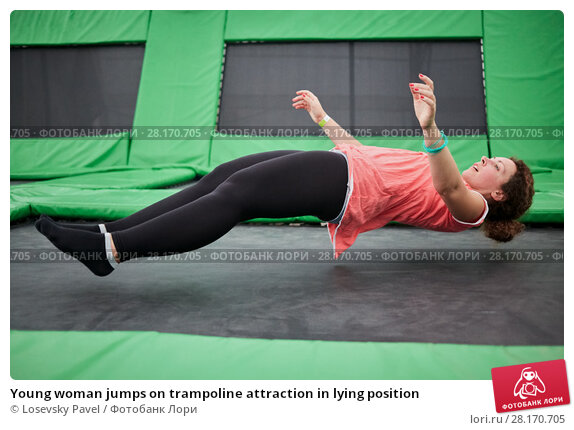 Купить «Young woman jumps on trampoline attraction in lying position», фото № 28170705, снято 29 августа 2016 г. (c) Losevsky Pavel / Фотобанк Лори