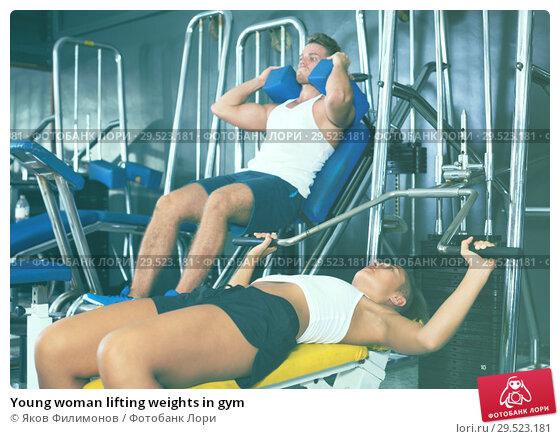 Купить «Young woman lifting weights in gym», фото № 29523181, снято 18 февраля 2019 г. (c) Яков Филимонов / Фотобанк Лори