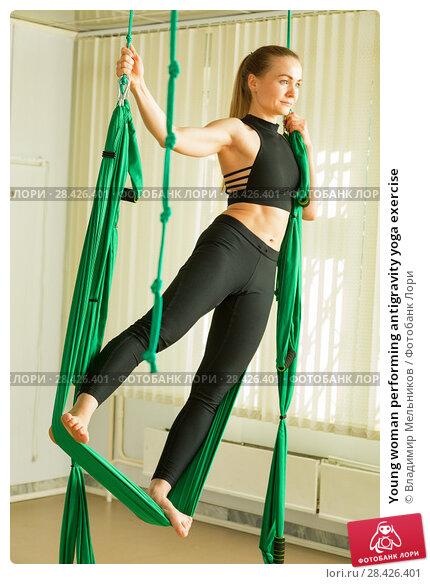 Купить «Young woman performing antigravity yoga exercise», фото № 28426401, снято 13 мая 2018 г. (c) Владимир Мельников / Фотобанк Лори